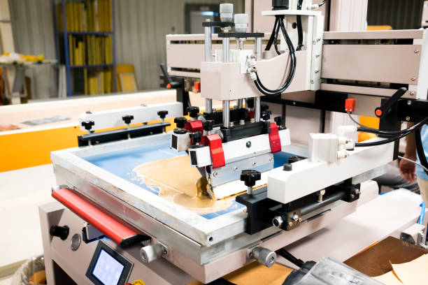 screen and digital printing machine in action inside packaging factory printing pouches stock photo