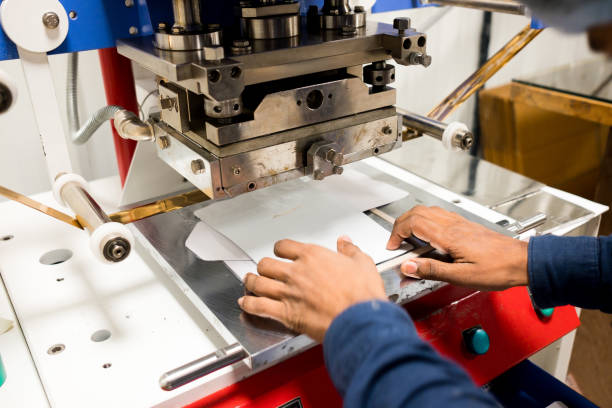 screen and digital printing machine operated by indian hands inside packaging factory printing plastic pouches stock photo