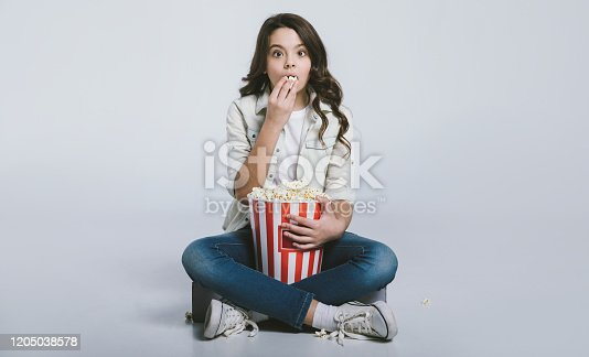 Focused child is sitting in a lotus position and eating popcorn, while watching cartoons or movies.