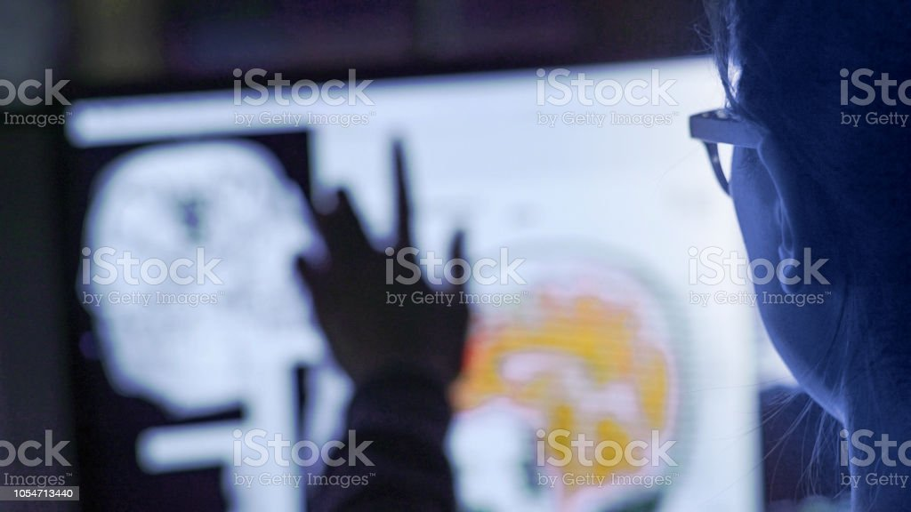 Screen physiology POV Close up image of a young asian woman using a large touch screen to look through healthcare images & moving images. This is shot over her shoulder and is near POV. Adult Stock Photo