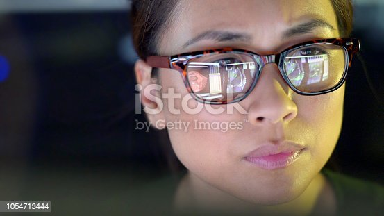Close up stock image of a young Chinese asian woman intently studying computer monitors showing medical data: MRI scans; x rays; CAT scans.