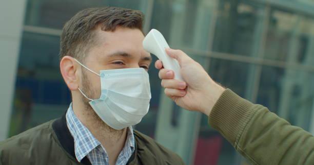 screening van passagiers, reizigers voor covid-19 coronavirus symptomen. mensen kunnen worden besmet door dodelijke coronavirus onderzocht, close-up schot. - sneakpreview stockfoto's en -beelden