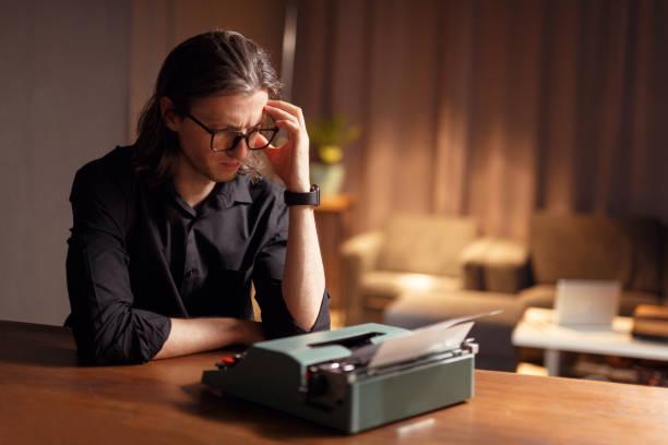 ein drehbuchautor in seinem büro, der an einem szenary arbeitet. mann in schwarzem hemd und brille hält hände in der nähe des kopfes, entwickelt filmische szenarien, isoliert auf einem verschwommenen innenraum. - drehbuchautor stock-fotos und bilder
