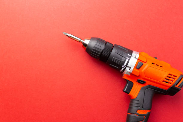 Screw driver with batteries on red background with place for text stock photo