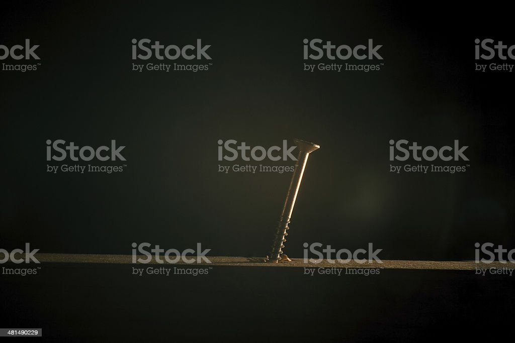 Screw in a plank of wood stock photo