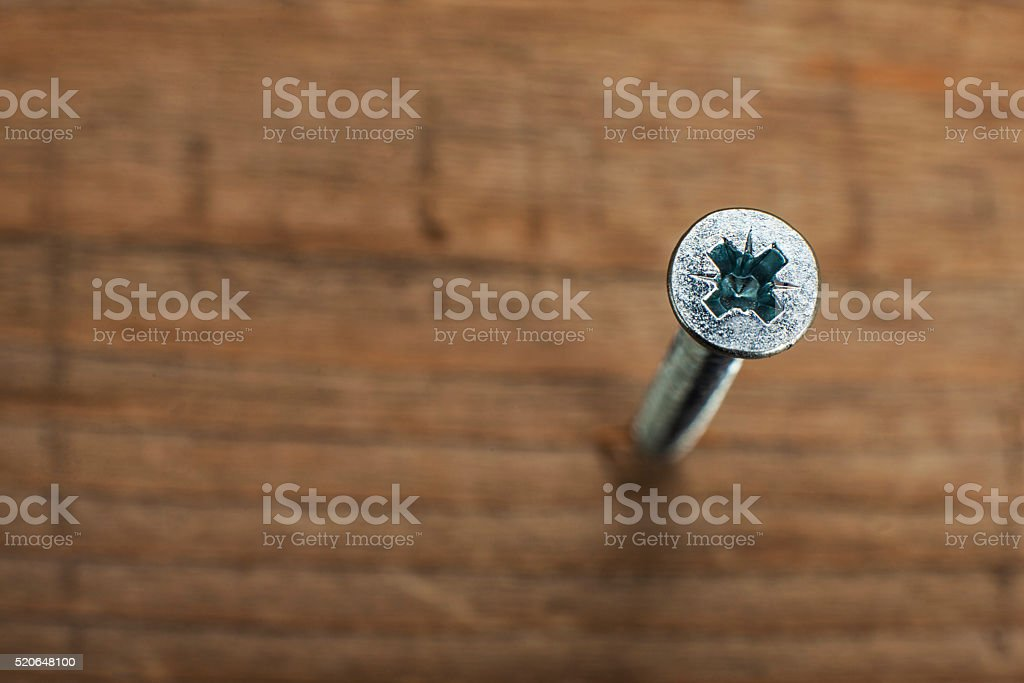 screw screwed into wooden plank stock photo