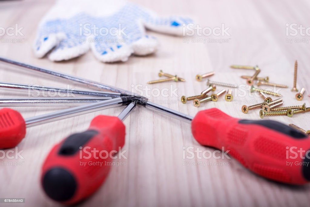 Screwdriver and set of screws on wooden background royalty-free stock photo