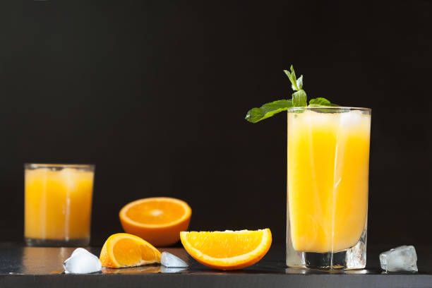 Screwdriver cocktail, orange juice with mint and ice. Screwdriver cocktail drink, orange juice with mint and ice in the dark copy space. screwdriver drink stock pictures, royalty-free photos & images