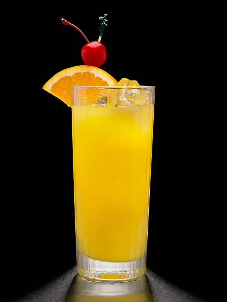 Screwdriver or Vodka and Orange Cocktail on black background A screwdriver, or Vodka and orange juice cocktail, shot on a black background and garnished with an orange and a cherry. screwdriver drink stock pictures, royalty-free photos & images