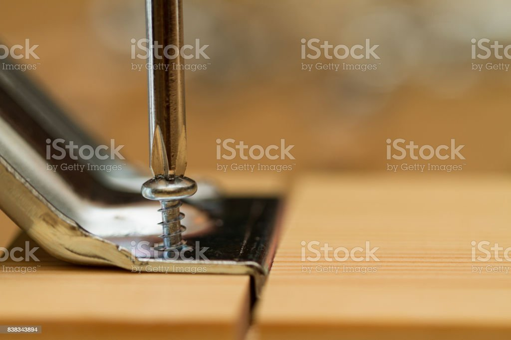 Screwdriver turning a screw stock photo