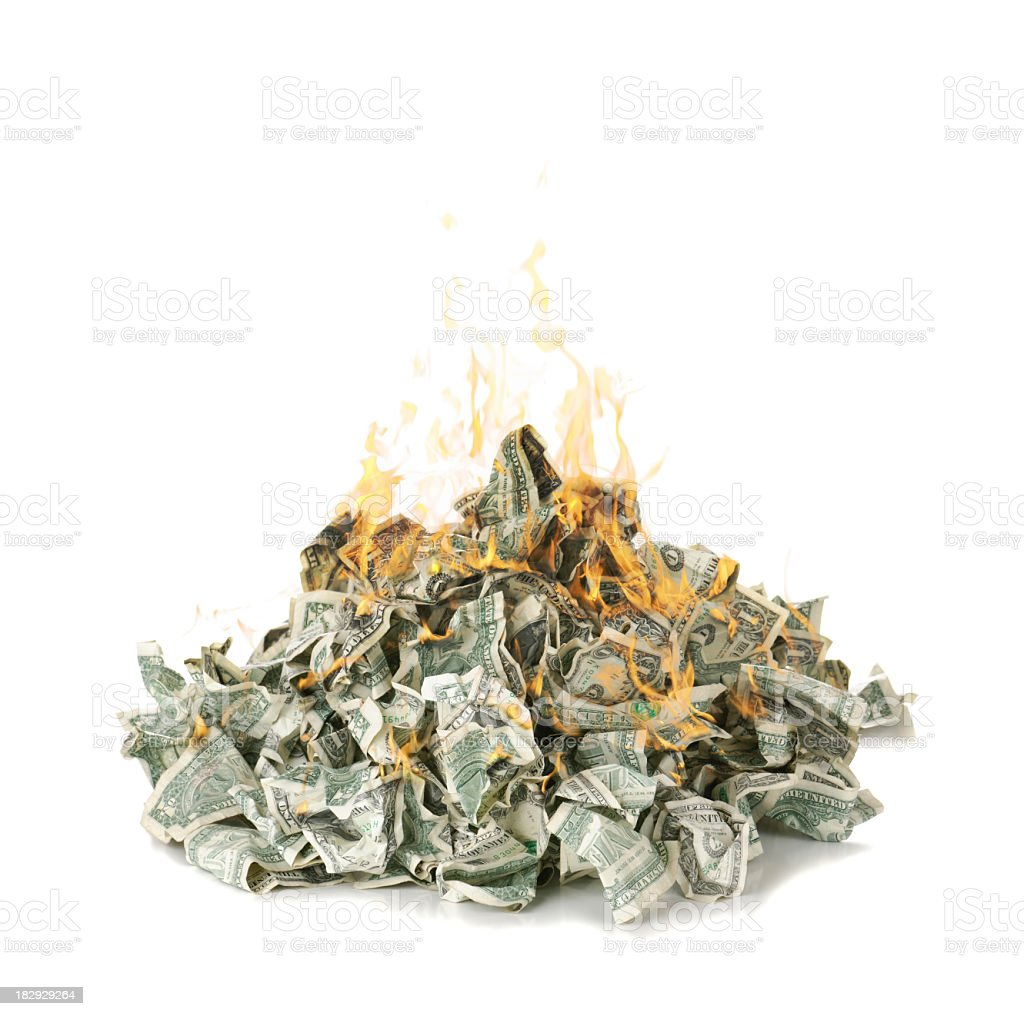Screwed up dollar notes in a pile on fire stock photo