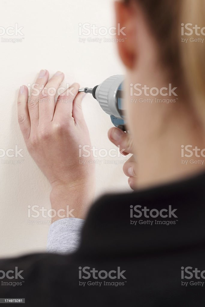 Screwing a screw into wall royalty-free stock photo