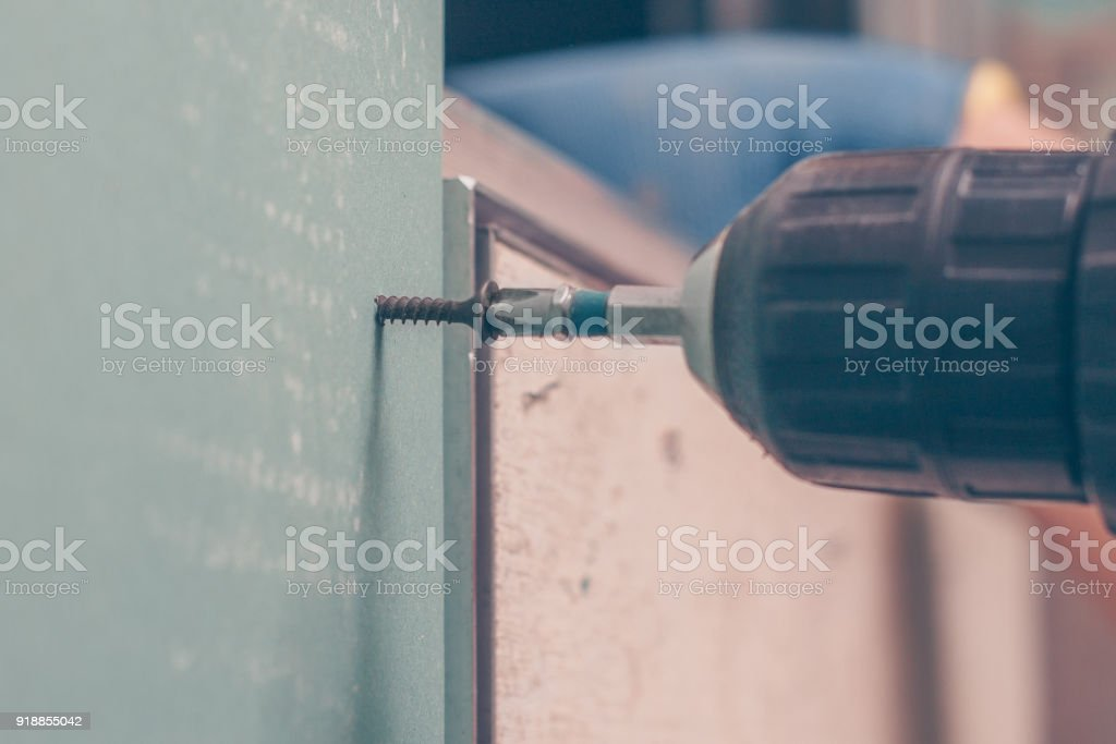 Screwing a self-tapping screw in a moisture-resistant gypsum board when installing a partition in the bathroom, close-up stock photo