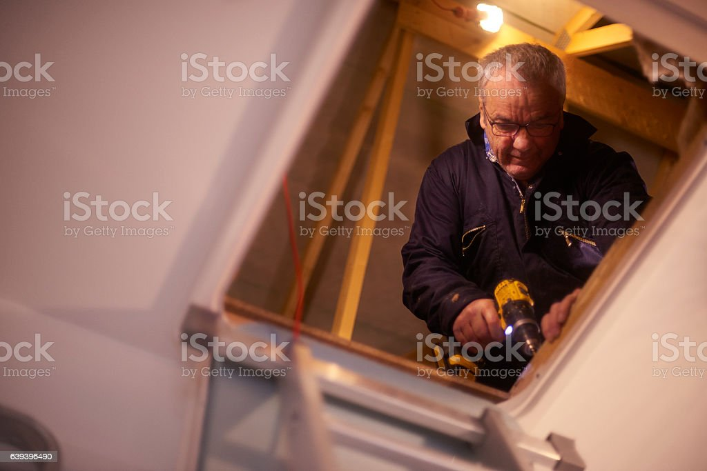 screwing down flooboard in the attic stock photo