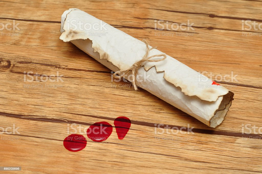 A scroll of paper tie up with rope  and three drops of blood stock photo
