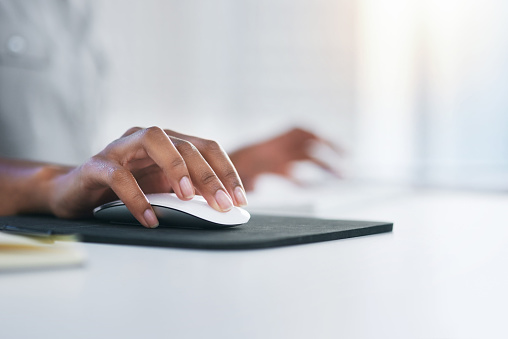 Closeup shot of an unrecognizable woman using a computer mouse in an office