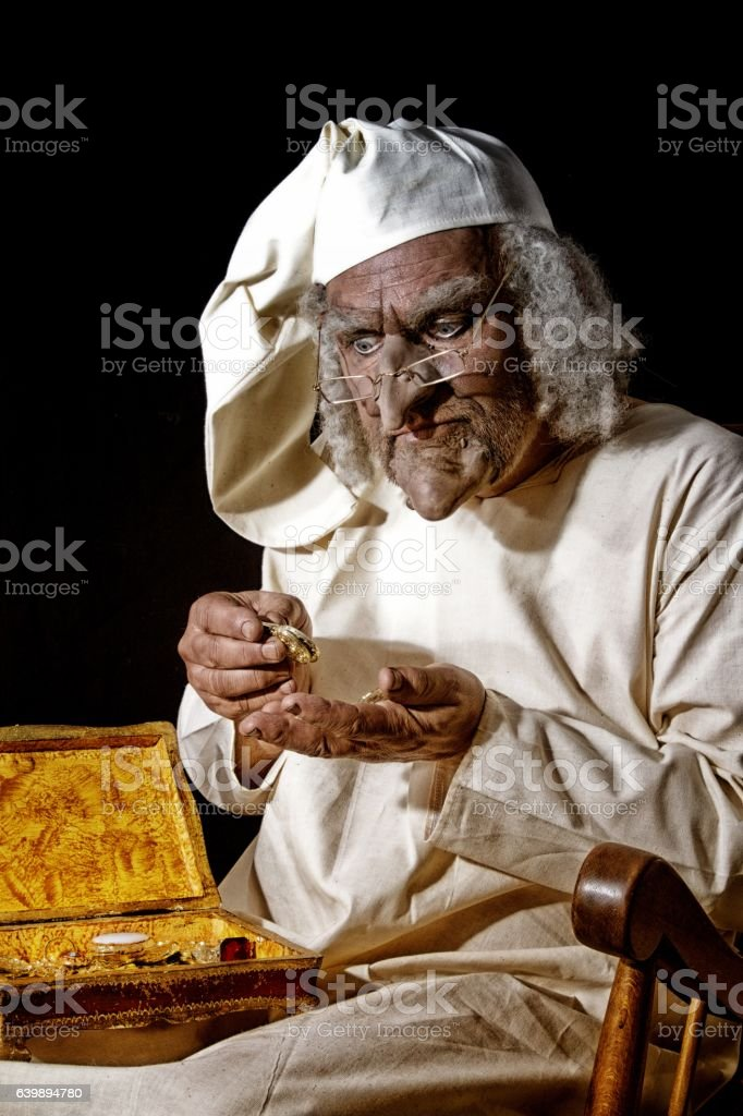 Scrooge like victorian character counting money - Photo