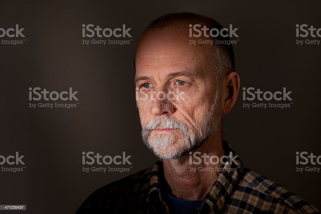 Scruffy looking senior adult man staring vacantly into the distance stock photo