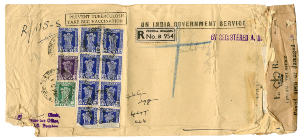 """Badly damaged envelope sent to England from Bombay, India, in 1961. The envelope bears a number of different messages including """"Prevent Tuberculosis, Take BCG Vaccination"""" and """"On India Government Service"""", as well as a sticker applied by the British General Post Office informing the recipient that the envelope had been found open. It was then secured by the official sticker."""