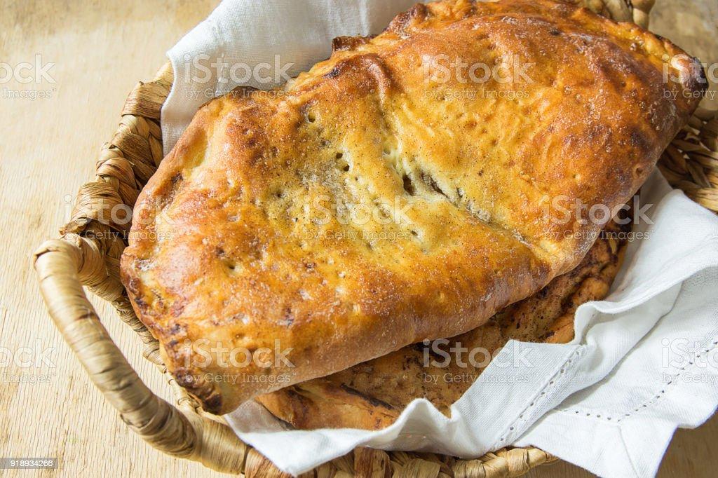 Deliciosa casa assado italiano pastelaria Calzone com torta de maçã doce passas canela enchimento na cesta de vime no guardanapo de linho branco. Tabela de madeira envelhecida. Cozinha rústica - foto de acervo
