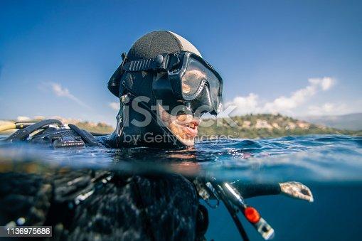 Portrait of scuba diver at sea surface preparing for dive underwater.