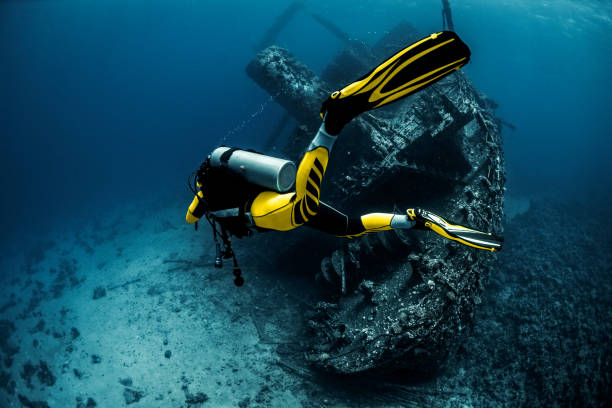 scuba diver circling a rusty old underwater shipwreck in the red sea - wreck diving stock pictures, royalty-free photos & images