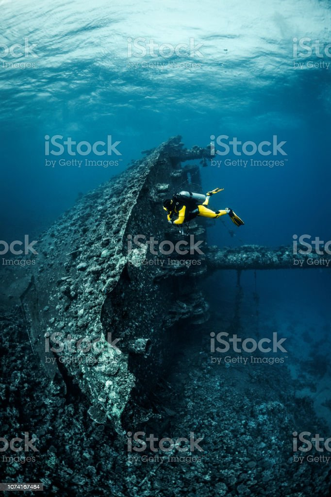 Scuba diver circling a shipwreck of a large size lying on it\'s side...