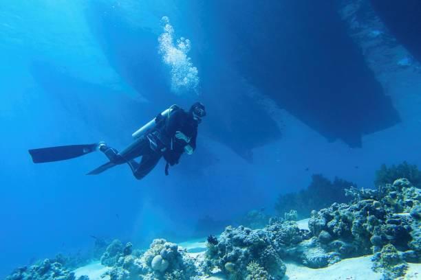 Scuba diver descending in to the sea, three boats silhouettes above him. stock photo