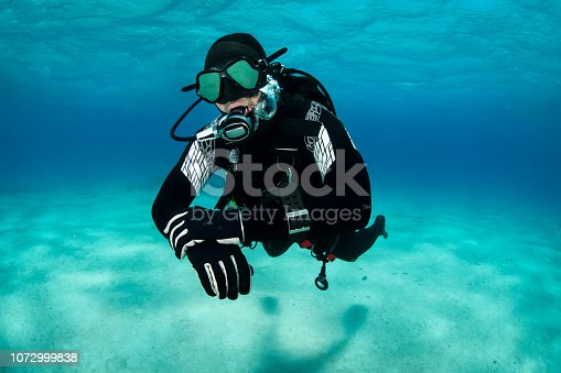 Scuba diver maintaining his depth in shallow waters of the Red Sea.