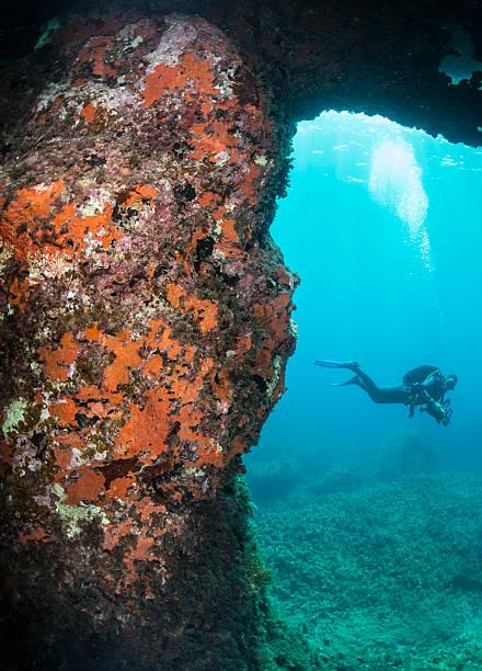 scuba diver exploring a rock formation stock photo