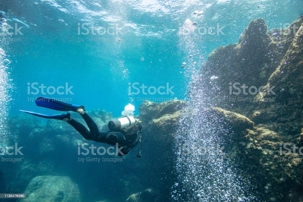 Scuba diver exploring reef stock photo