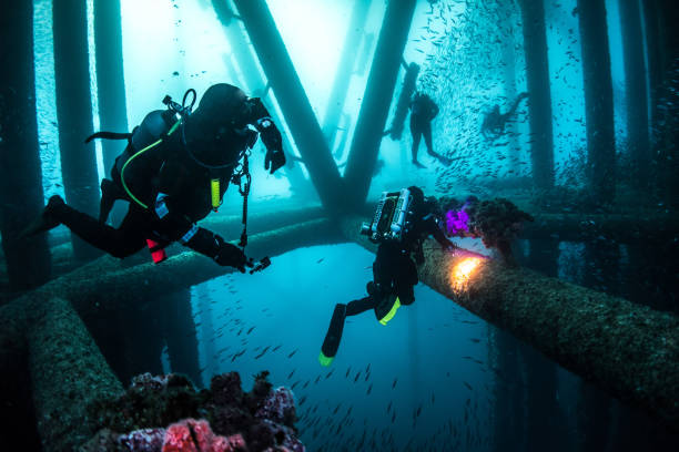 scuba diver group under oil rig platform - wreck diving stock pictures, royalty-free photos & images