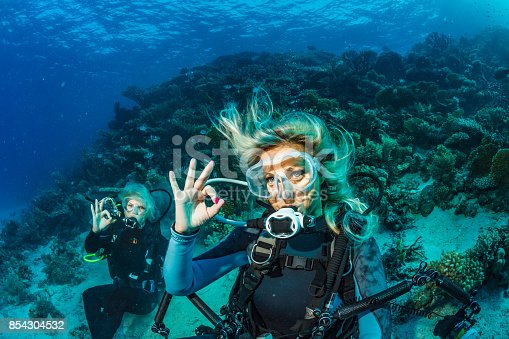 istock Scuba diver is exploring and enjoying Coral reef  Sea life Couple Two sporting women Underwater photographer 854304532