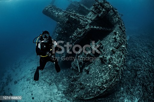 Scuba diver in a black wetsuit maintaining his depth next to a large sunken ship in the red sea.