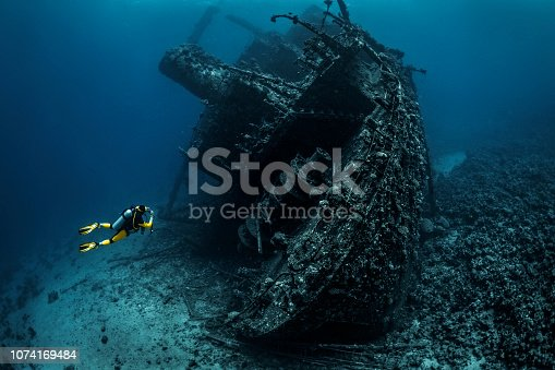 Scuba diver passing by a wreckage of a large sunken ship in the Red Sea.