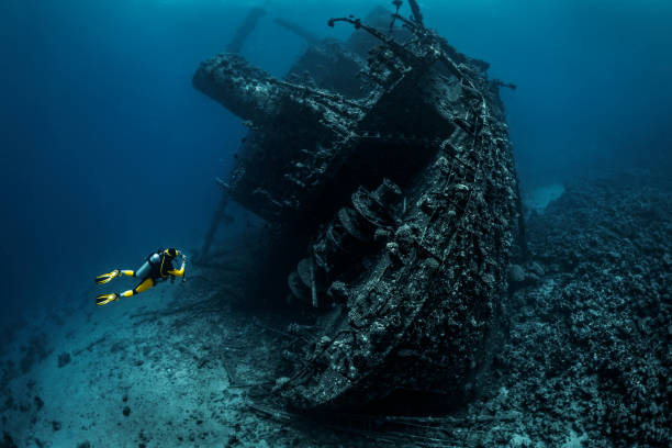 scuba diver observing a large shipwreck completely rusted and overgrown lying underwater in the red sea - shipwreck stock pictures, royalty-free photos & images