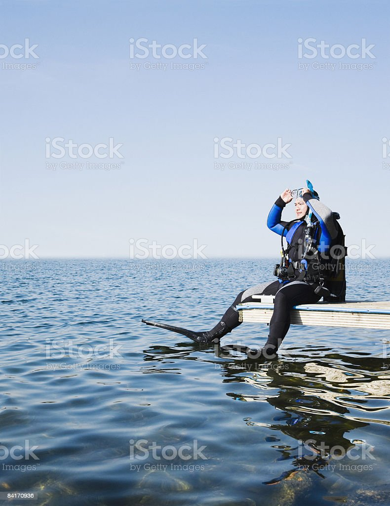 Scuba diver preparing to dive off a jetty royalty-free stock photo