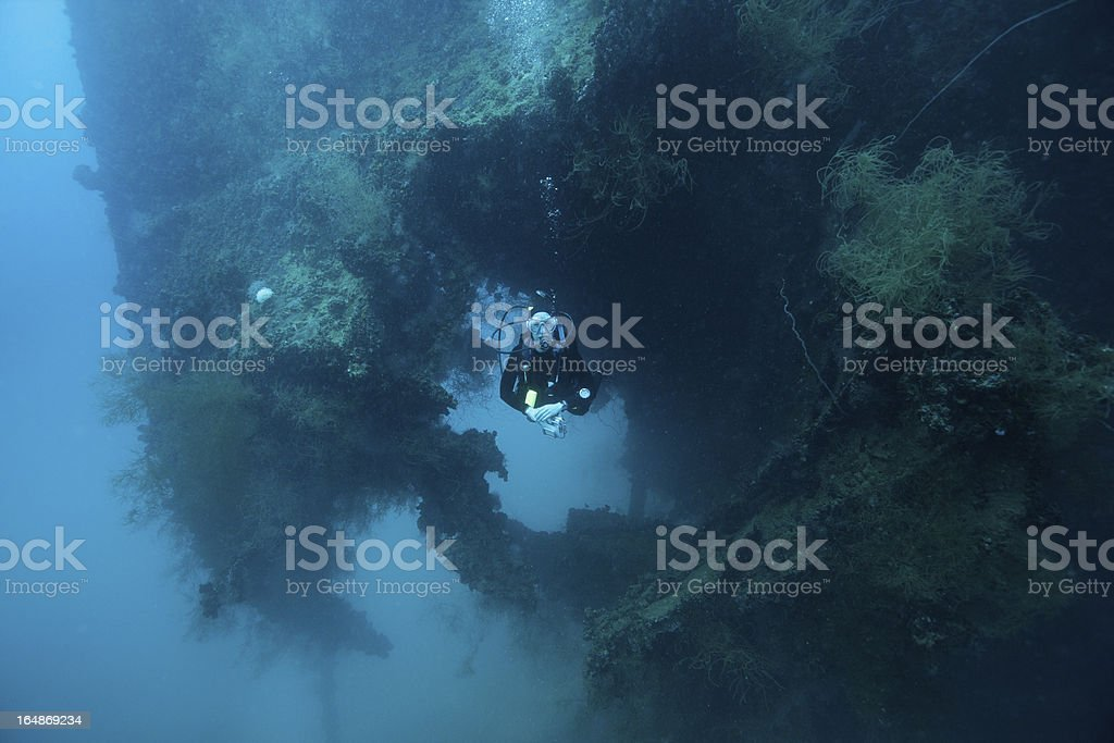 Scuba diver swimming through a hole in the hull of stock photo