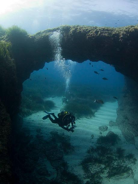 scuba diver swims through an underwater arch stock photo