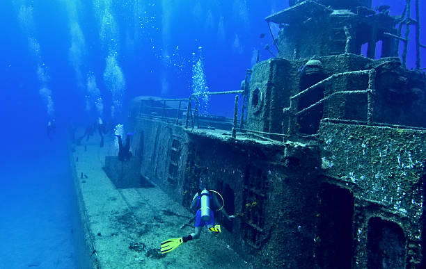 scuba divers explore a wreck - wreck diving stock pictures, royalty-free photos & images