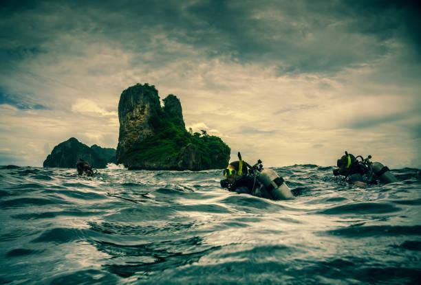 taucher-oberfläche bei twilight, ko bida, phi phi, thailand - rettungsinsel stock-fotos und bilder