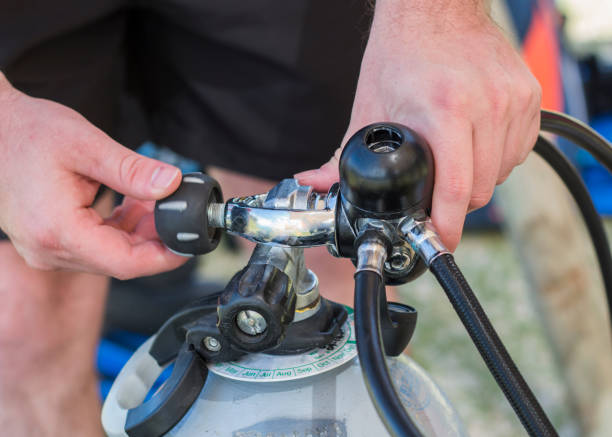 Scuba diving equipment close up of a man attaching an A-clamp regulator to a cylinder. stock photo