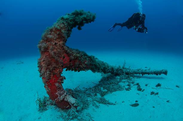 scuba diving on an old anchor stock photo