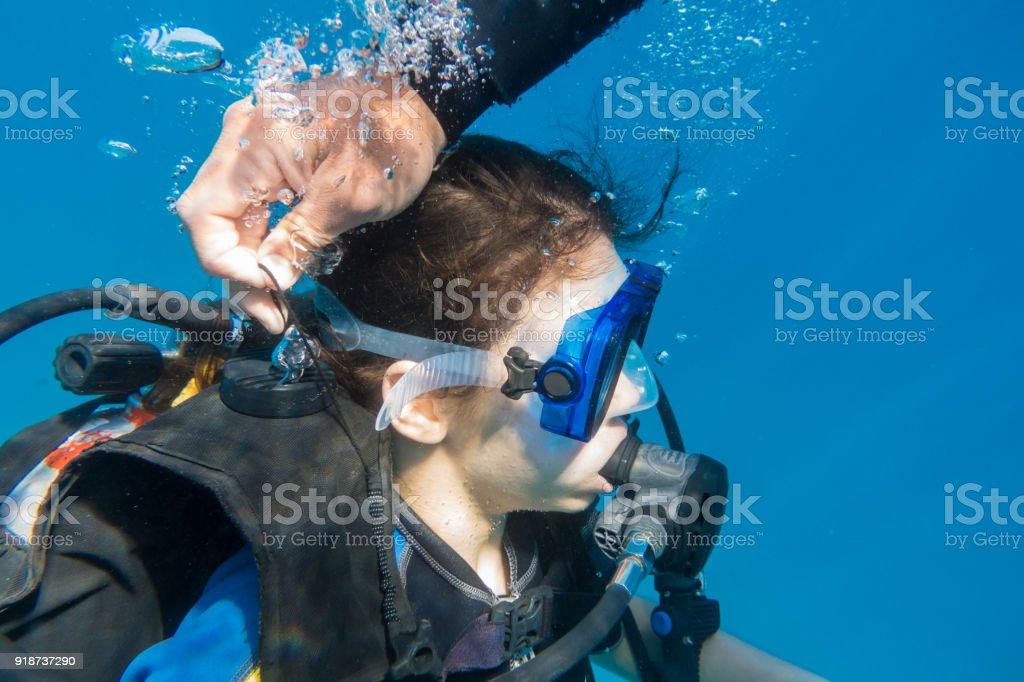 Instrutor de mergulho abriu a válvula de ar na roupa de mergulho para mergulhar - foto de acervo