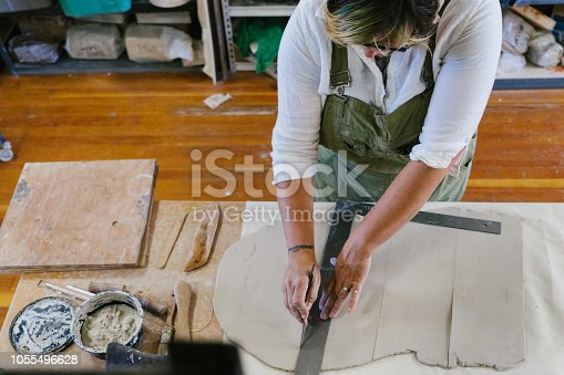 Mid adult woman creating ceramic sculpture