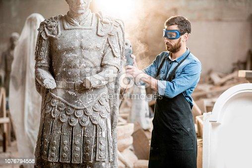istock Sculptor grinding sculpture in the studio 1076794558