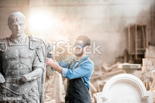 istock Sculptor grinding sculpture in the studio 1076794584