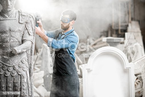 istock Sculptor grinding sculpture in the studio 1076794596