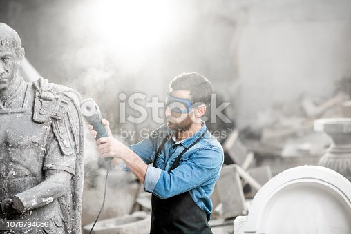 istock Sculptor grinding sculpture in the studio 1076794656