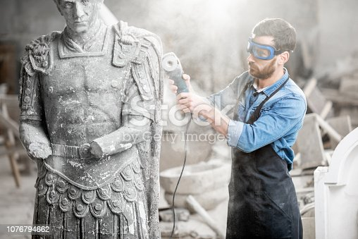 istock Sculptor grinding sculpture in the studio 1076794662